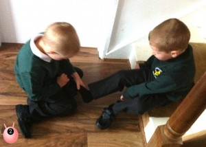 Brother helping his younger brother put his shoes on for his first day of school