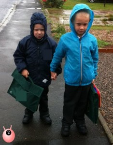 Brothers holding hands walking together in the rain on the school run