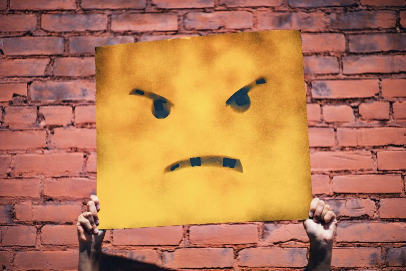paper square angry face,held up in front of a brick wall