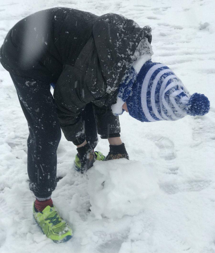 boy rolling a giant snowball to make a snowman base