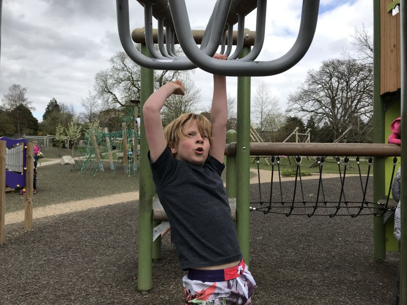 boy swinging on monkey bars